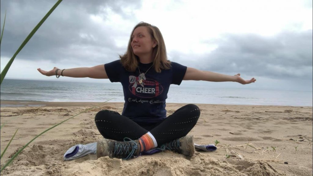 Amanda on the beach with her hands stretched out. Knowing that she has beat depression.