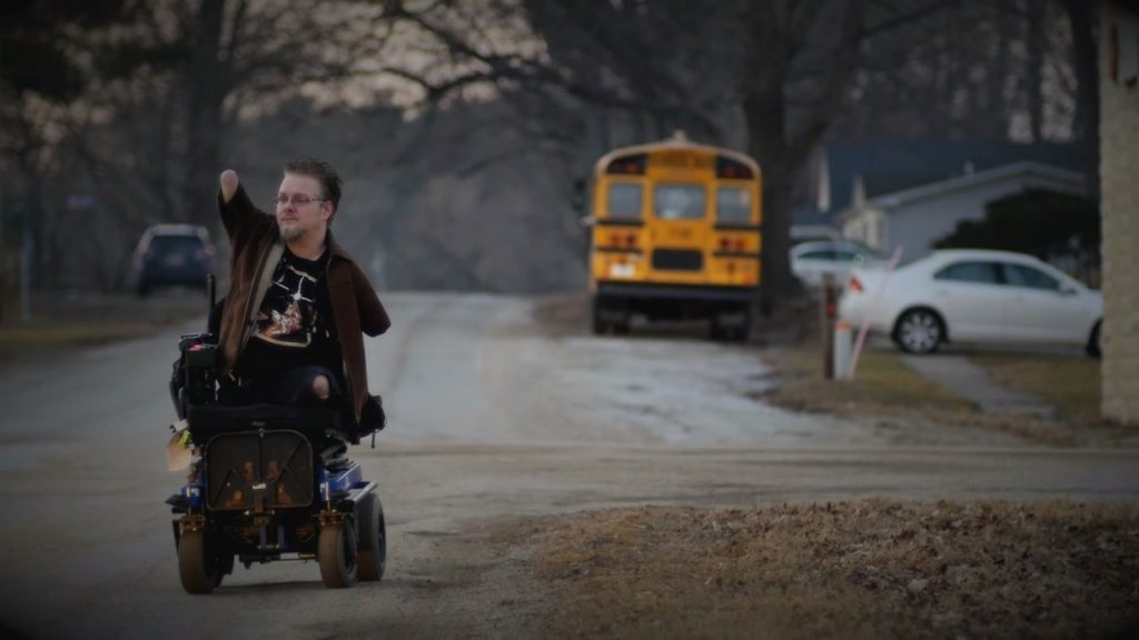 Brett waving to his neighbors. This everyday hero proves overcoming obstacles has made his life great.